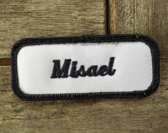 "Miseal. A white work shirt patch that says ""Miseal"" in dark blue script with dark blue border"