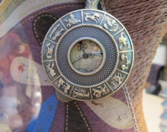 A Pocket Watch With the Astrological signs on the Front Cover