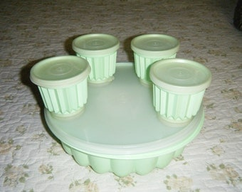VINTAGE TUPPERWARE MOLD.  Large green tupperware mold with lid and four small molds with lids as well.  great condition.