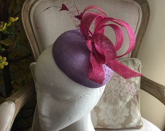 Gorgeous lilac/purple round fascinator with magenta loops, feathers and netting. Stunning!