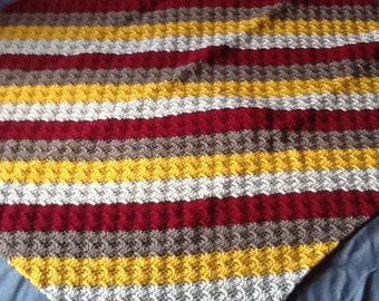 Crocheted lap afghan in reds, tans, golds and browns