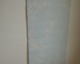 Wall hanging, wall decoration.  Roller blind fabric with white blossom, pale blue background.  Pockets for dowel/weight bar to hang on wall