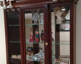 This is a display cabinet that is hung on the wall but could also be free standing on a counter or a table.