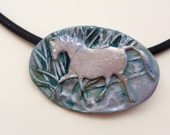 Silver horse trotting  through the woods pendant with blue background.