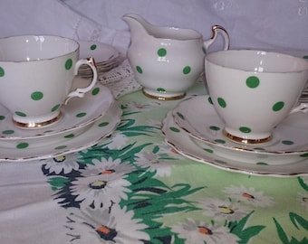 Two white with green polka dots china cup, saucer and tea plate trios. One cup has chip so charged for only one set.