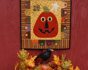 A Whimsical Jack-O-Lantern handmade quilted wall hanging in rich fall colors.