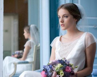 Un voile romantique, orné d'un ruban satiné, brodé de perles délicates, entrelacés de fils argentés  forment une ravissante chaine de fleurs