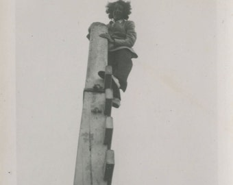 Vintage snapshot photograph of a woman climbing a high pole looking down