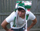Two-Tail crochet elf hat in white, green, and red with ear flaps and braided tassels. Adult unisex.