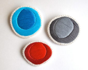 Hand embroidered brooch set of three geometric spheres in blue, red and gray on cream muslin with cream felt backing