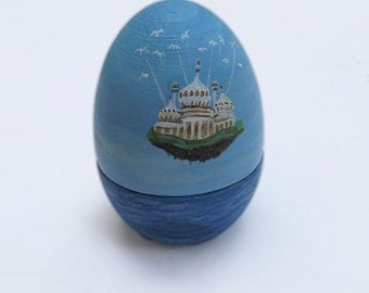 Painted wooden egg. Hollow egg with a painting of Brighton Pavilion flying over the sea, carried by seagulls. Perfect to hide a ring inside!