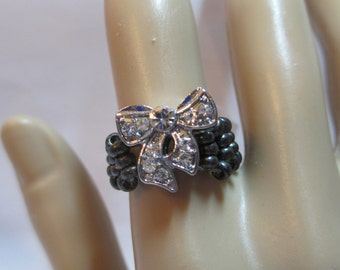 Ring with charcoal gray beads with silver metal bow with crystals on stretchy cord size 7, 8