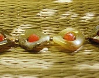 Creamy-green soocho jade frames faceted Carnelian beads in a bracelet.