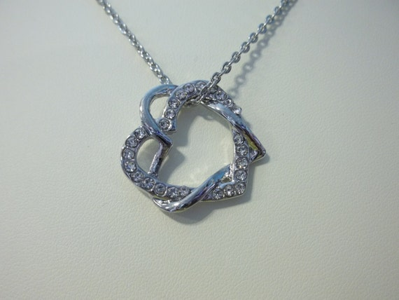 Two silver hearts intertwined