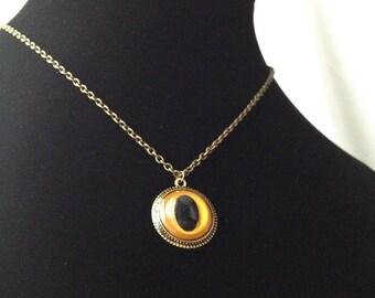 "Yellow Cat/Snake Eye Pendant. Brass tone chain is 15.75"" long."