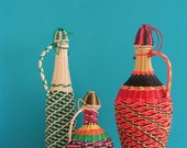 Vintage set of three multi color glass bottles, vases , wickered with nylon wire, 1960s, dinner party, picnic, serving
