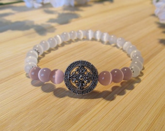 White and light lilac bracelet with a silver charm.