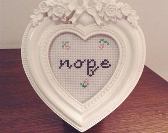 "Cute ""nope"" cross stitch in heart shaped frame."