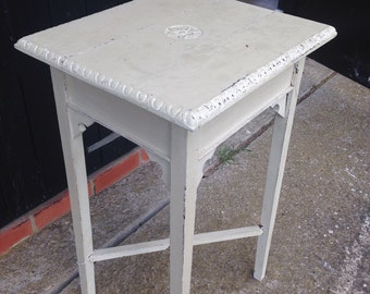 Antique style table with carved detail on top.