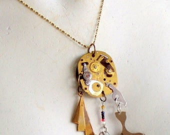 Handcrafted wearable sculpture pendant necklace featuring vintage watch parts, glass beads, brass accents.
