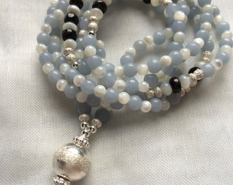 Mala made of light blue Angelit (anhydrite) and Astrophyllit, decorated with mother of Pearl and silver end bead silver,