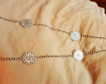 Long silver chain necklace with silver medallions between sections of chain with a claw clasp