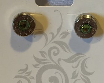 S&W 40 caliber stud earrings with green gem.