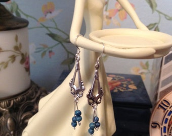 Silver tone earrings with blue bead and heart dangles