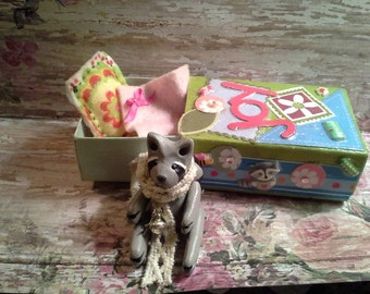 """Annabella"""" Handmade clay raccoon with movable arms and legs. Matchbox bed and handmade tea set included!"""