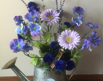 Tin watering can with artificial flowers