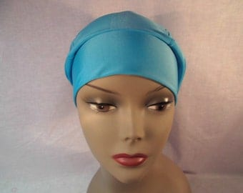 Pretty sluchy blue cap with wide band, has room for a scarf under it. Works well as a head cover,hat,messy hair.
