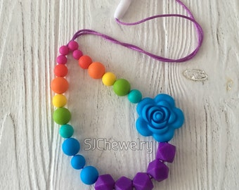 Rainbow Colored Teething&Nursing Necklace with a sky blue flower bead