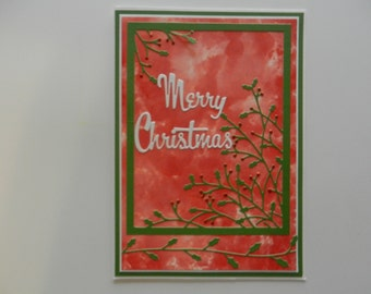 Christmas card with holly in red, white and green.