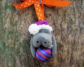 Santa Manatee Holding Purple Christmas Ball Ornament