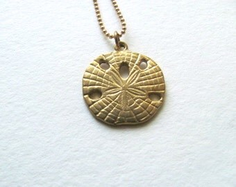 Gold sand dollar necklace, brass charm on 14k gold plate chain