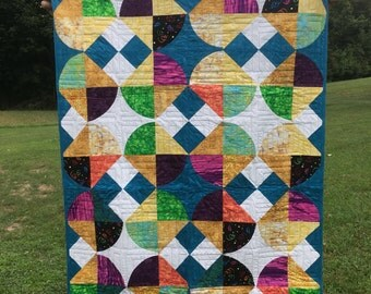 This whirling colorful quilt with a drunkard's path pattern