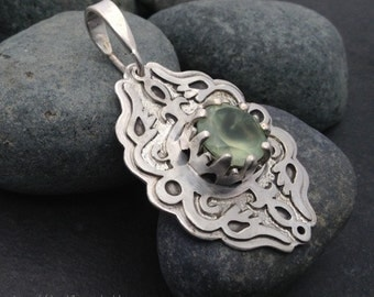 Medium sized solid sterling pendant, with a faceted pale green prehnite, hand cut prong crown setting, ornate layered silver cutwork