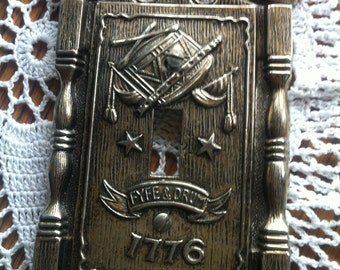 A Metal Switch Plate Cover That Reads Fyfe & Drum 1776 By American Tack Hdwe. Co 1968