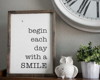begin each day with a smile. 19.5 x 14 distressed wood sign. white with black writing.