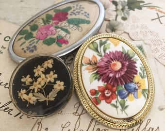 Three vintage floral brooches and a scarf clip