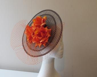 Handmade sinamay double base chocolate coloured  fascinator embellished with orange merry widow veiling and orange roses.