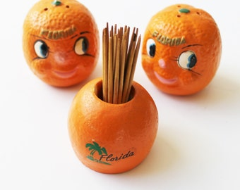 Kitschy Florida souvenir salt and pepper shakers and orange toothpick holder, anthropomorphic oranges, travel memorabilia, Florida souvenir