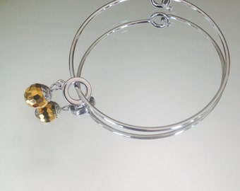 Nickel free silver tone bangle bracelet with gold/auburn disco ball charm