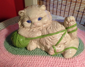 Large vintage white kitty playing with a green yarn ball.