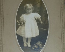 Edwardian cabinet card of an adorable little girl holding flowers