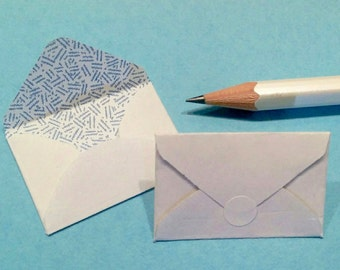 Miniature envelopes made from salvaged paper