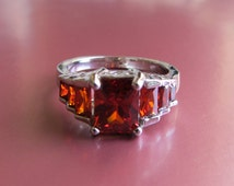 Sterling Silver Plate Deep Red Orange CZ Stones(?) in Step Setting. Sz 7+