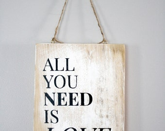"""Wooden sign with Inscription """"All you need is love"""""""