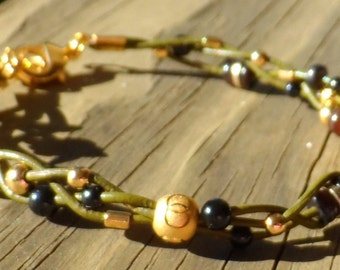 Women's 7 inch bracelet in braided green leather with gold plated and black beads