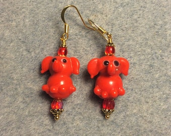 Opaque bright red lampwork sitting elephant bead earrings adorned with red Czech glass beads.